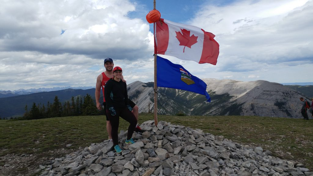 An image of two people standing at the top of Prairie Mountain in Alberta, Canada