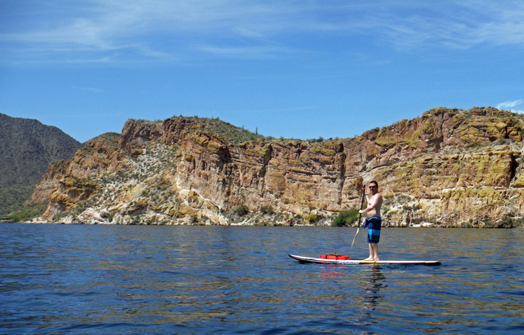 An image of a man on a stand-up paddleboard on Saguaro Lake