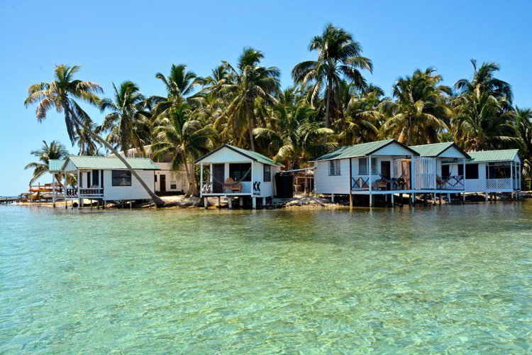 An image of over-the-water bungalows on Tobacco Cay Paradise in Belize.