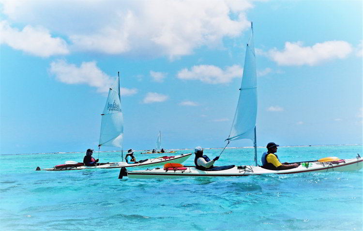 An image of three kayaks with sails sailing in Belize through the South Water Caye Marine Reserve