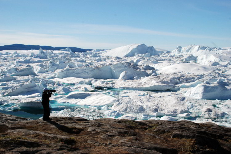 An image of a photographer taking a picture of the Ilulissat Icefjord in Ilulissat Greenland