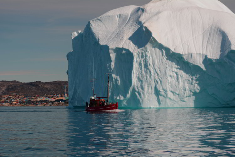 An image of a boat, a massive iceberg and the town of Ilulissat Greenland