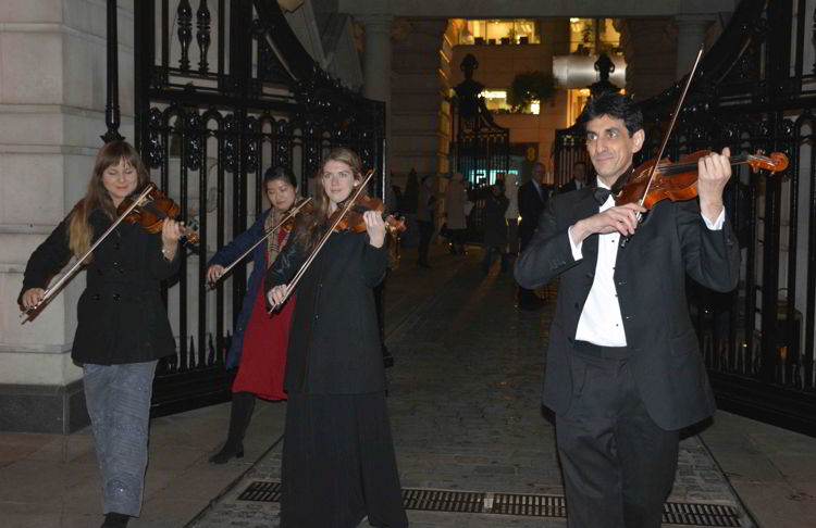 An image of some musicians playing violins - best Christmas markets