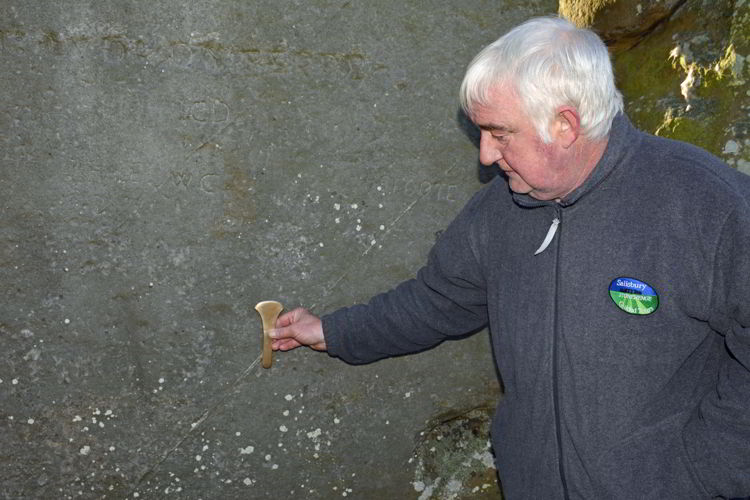 An image of guide Pat Shelley pointing to a stone at the Stonehenge site near Salisbury, UK - Stonehenge inner circle tours