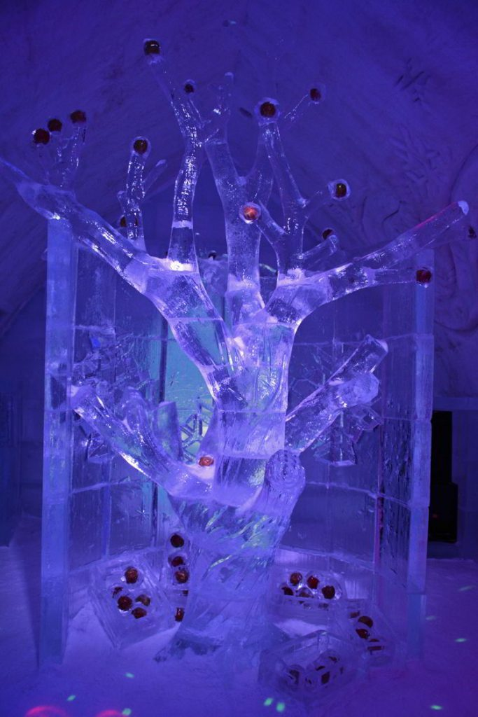 An image of an ice scupture of  frozen apple tree inside the Hôtel de Glace in Quebecm Canada - Ice Hotels Quebec.