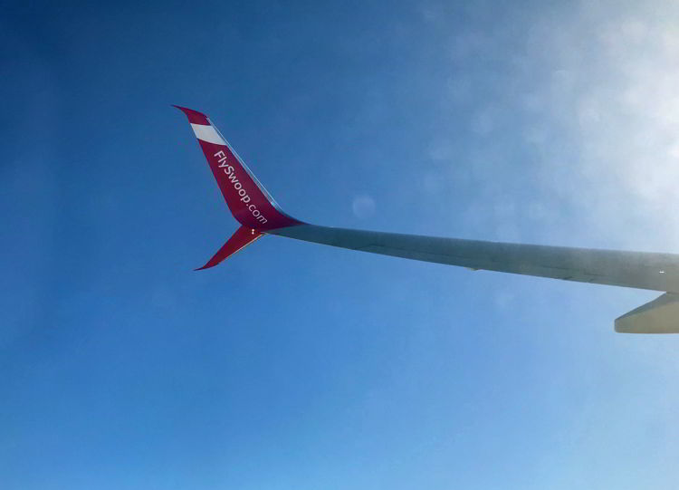 An image of a Swoop Airlines aircraft wing in the air - Swoop Airlines review