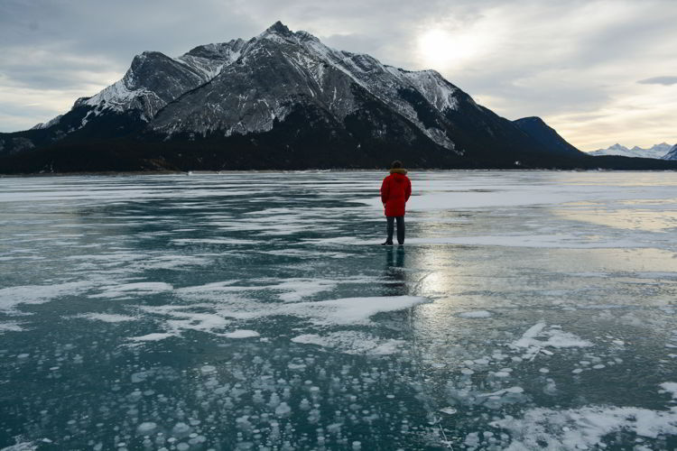 An image of a man standing on Abraham Lake in winter with ice bubbles in the foreground - Abraham Lake, Alberta