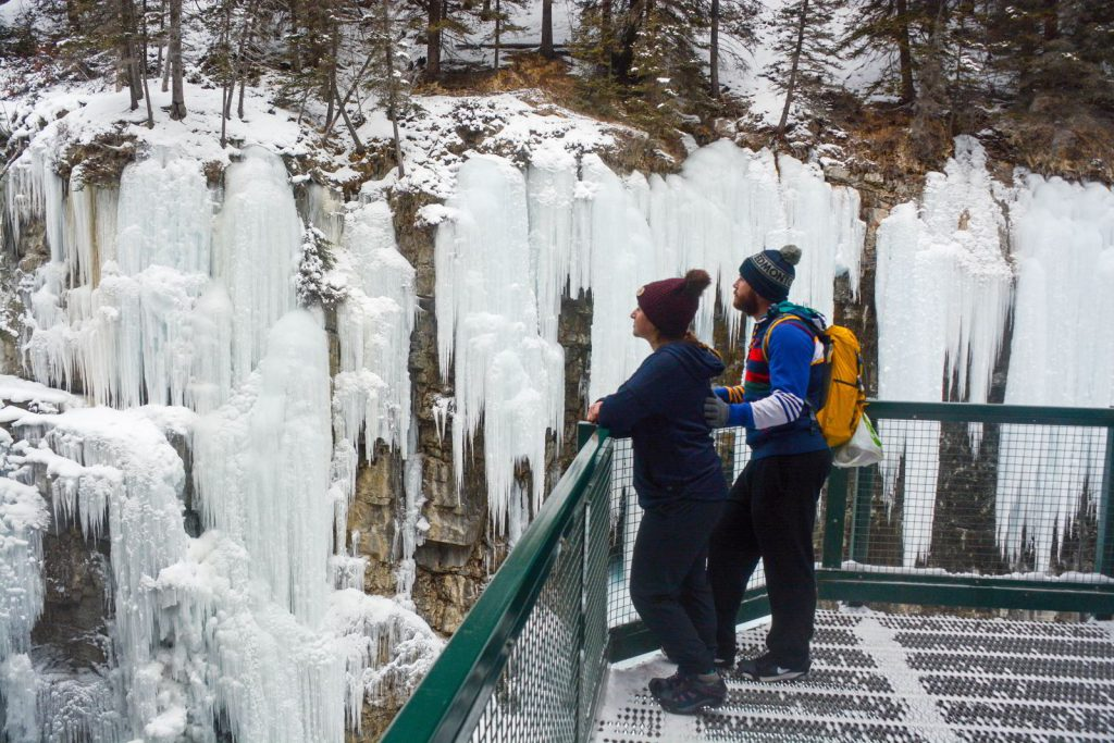 An image of two people looking at the ice formations in Johnston Canyon in Banff National Park - Johnston Canyon Winter Hike