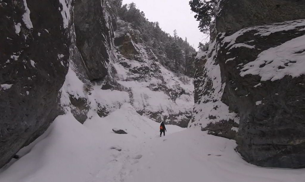 An image of a hiker walking through the frozen Grotto Canyon hike near Canmore, Alberta.