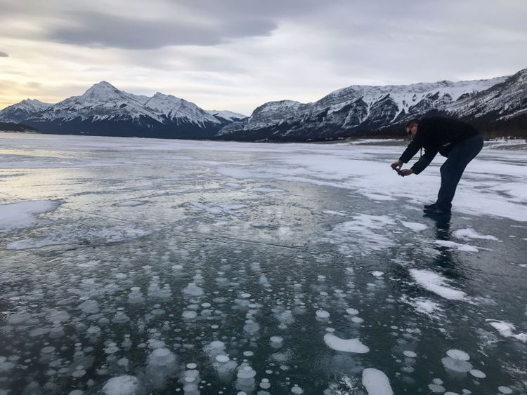 An image of a man taking a photograph of the ice bubbles in Abraham Lake, Alberta