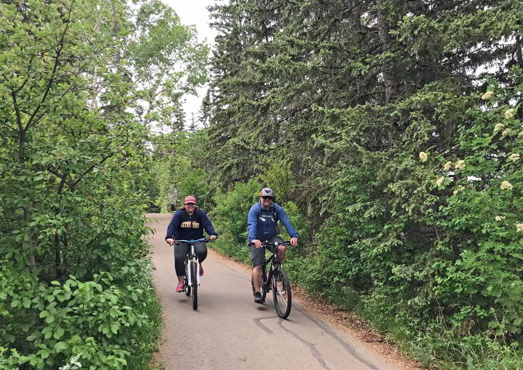 An image of two people cycling on the trails in Waskasoo Park in Red Deer, Alberta, Canada.