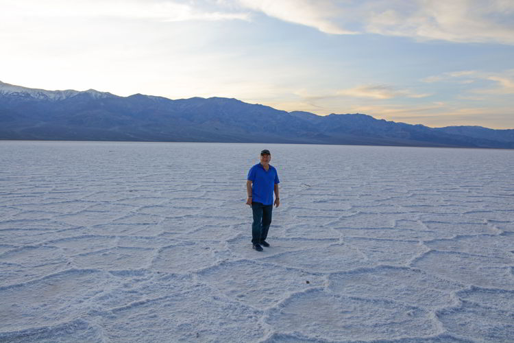 An image of a man standing on the Badwater Basin salt flats in Death Valley National Park in California - visiting Death Valley