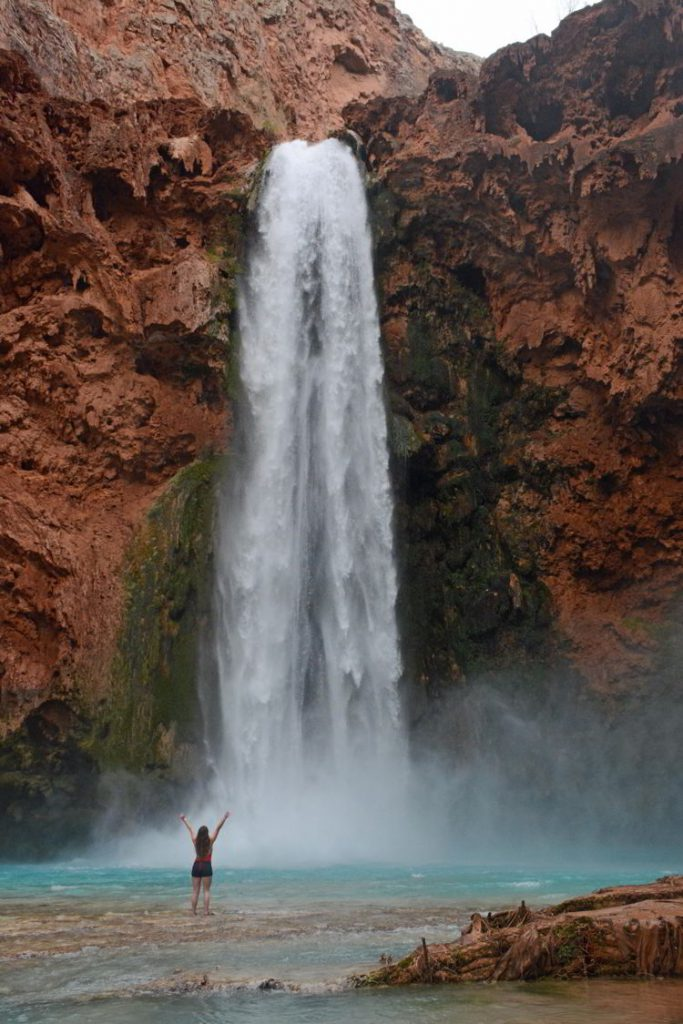 An image of a woman standing in front of Mooney Falls - Havasupai Hike