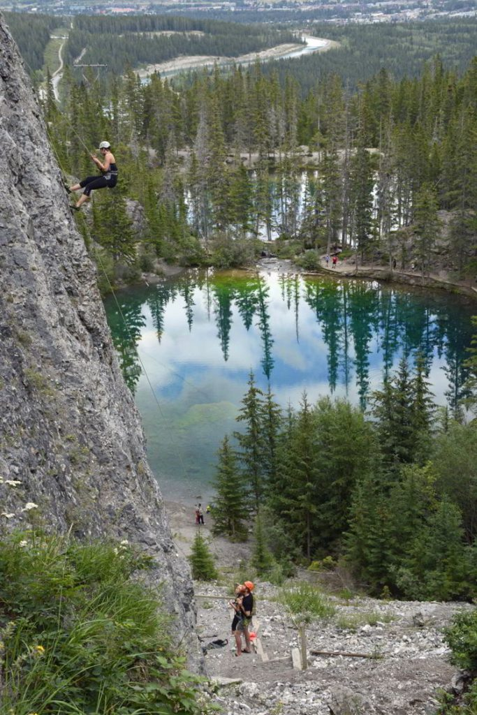 An image of some rock climbers scaling a cliff face above the Grassi Lakes near Canmore, Alberta in the Canadian Rockies.