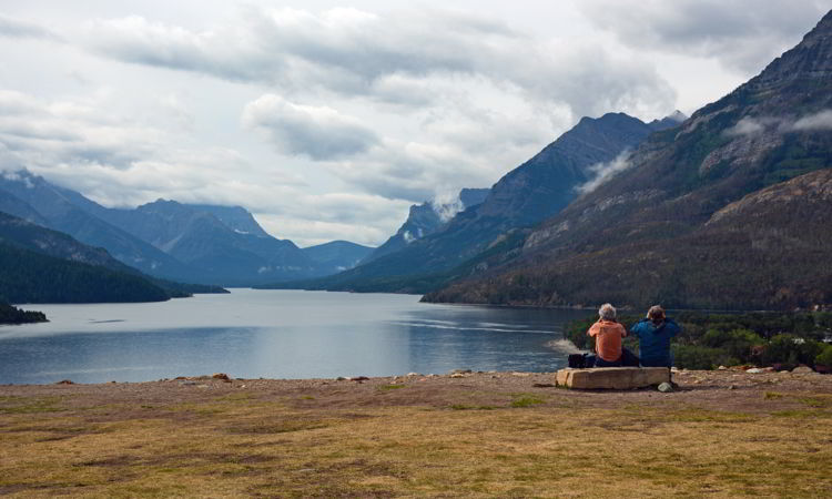 An image of two people taking in the view from the bluff behind the Prince of Wales Hotel in Waterton Lakes National Park in Alberta, Canada.