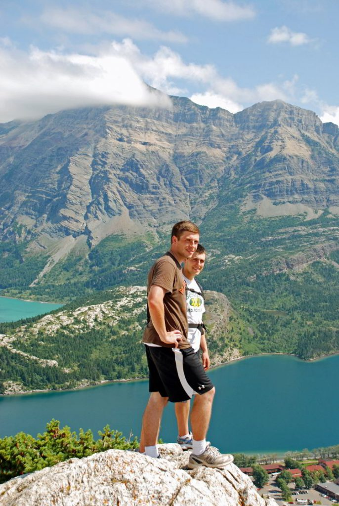 An image of two young men standing at the top of the Bear's Hump hike in Waterton Lakes National Park in Alberta, Canada.