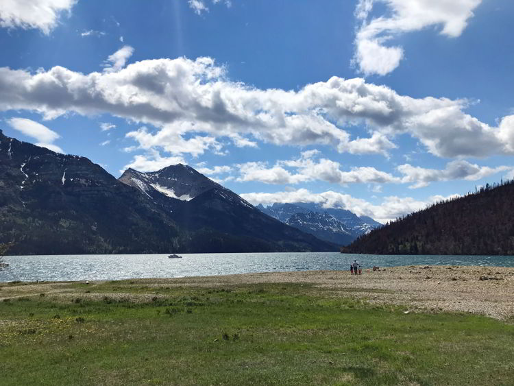 An image of an adult and two young boys standing on the shores of Upper Waterton Lake in Waterton National Park in Alberta, Canada.