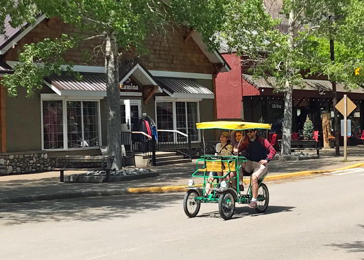 An image of a dad and his two daughters riding a surry bike in downtown Waterton