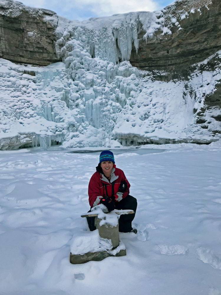 An image of a person kneeling on the ice in front of Crescent Falls in winter - Crescent Falls hike.