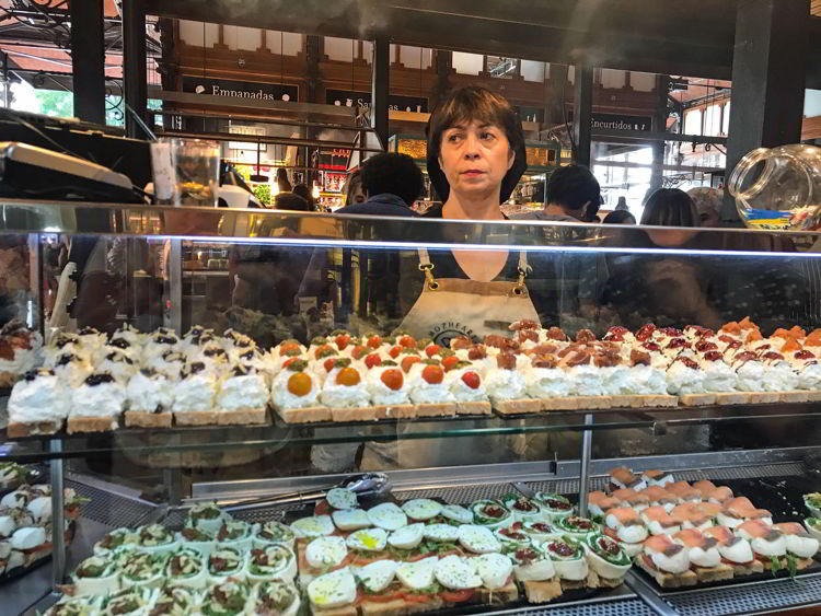 An image of a tapas vendor standing behind a counter at the Mercado de San Miguel in Madrid, Spain.