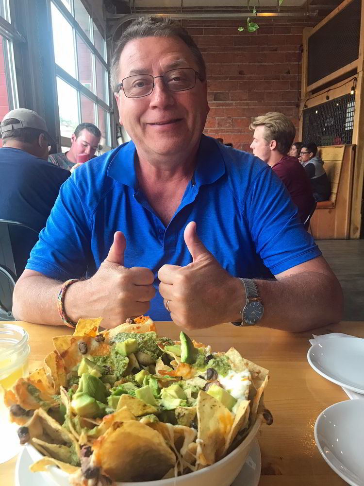An image of a man giving two thumbs up to the nachos at Fire Hall Kitchen & Tap in Cranbrook, BC.
