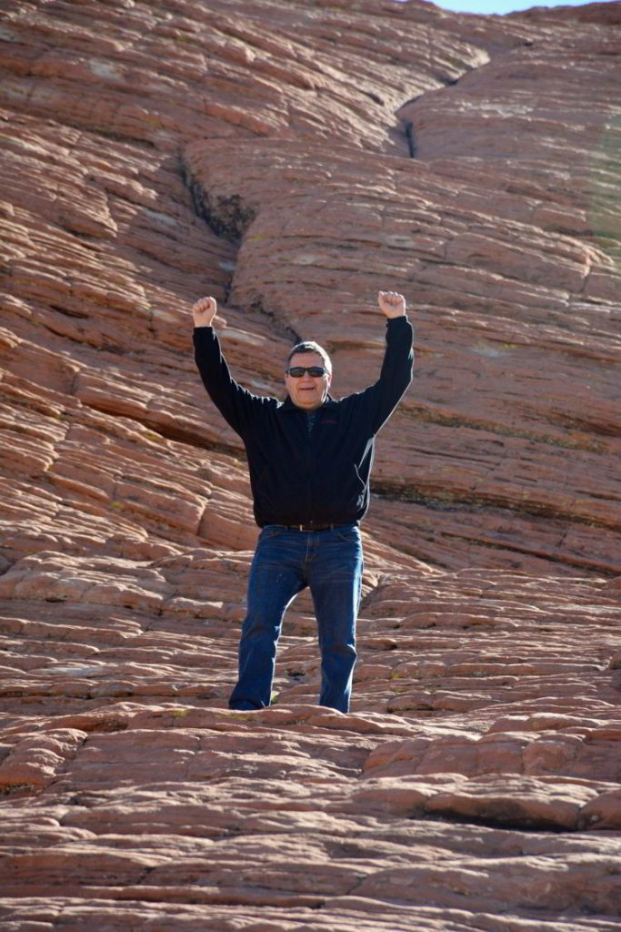 An image of a man standing on the red rocks at Red Rock Canyon Conservation Area outside Las Vegas, Nevada.