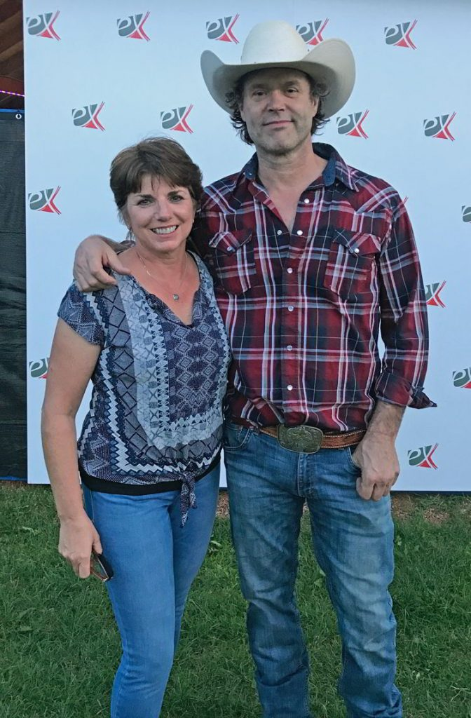 An image of a woman standing next to Corb Lund at Whoop-up Days in Lethbridge, Alberta.