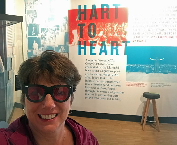 An image of a woman taking a selfie at the Corey Hart exhibit at National Music Centre in Calgary, Alberta, Canada.