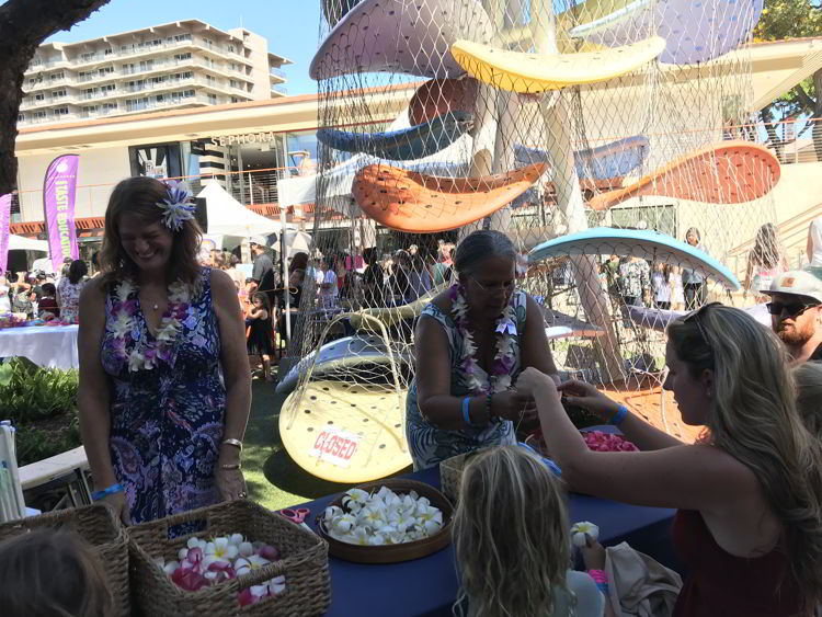 An image of children making flower leis at the Keiki in the Kitchen event of the Hawaii Food and Wine Festival in Kāʻanapali, Maui.