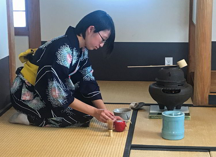 An image of a woman pouring tea in a traditional Japanese tea ceremony at the Nikka Yuko Japanese Gardens in Lethbridge, Alberta
