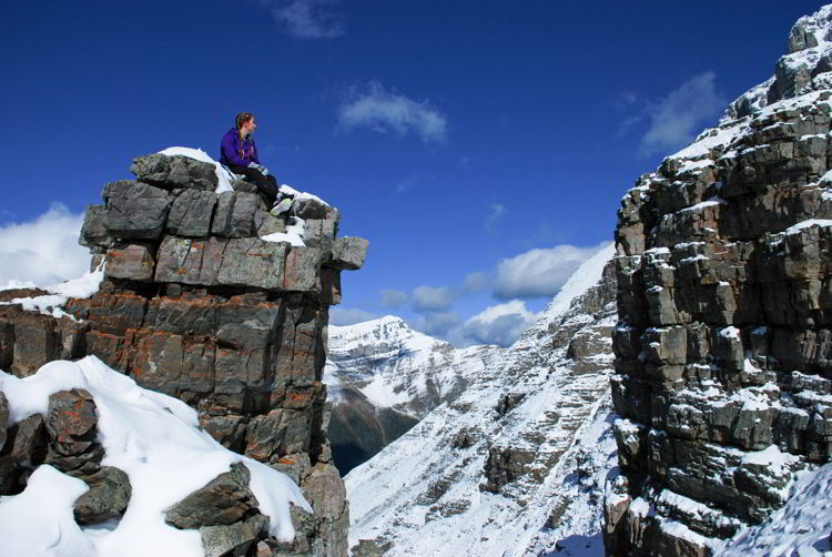 An image of a young woman sitting on a rock outcropping near the top of Sentinel Pass in Banff National Park, Alberta, Canada.