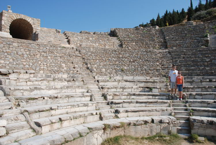 An image of two people standing on the steps of the great theatre in Ephesus.
