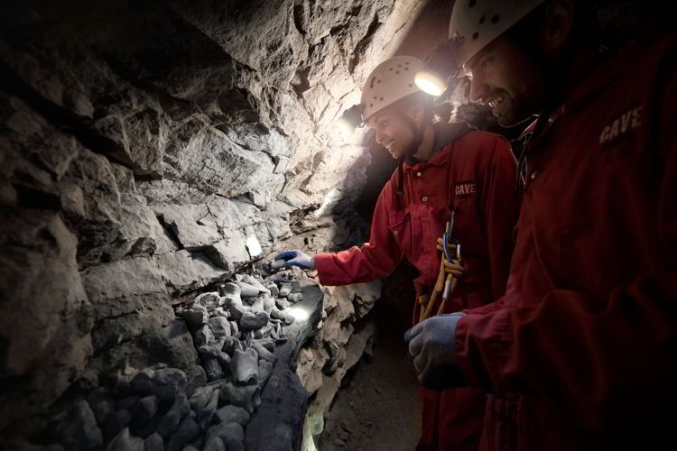An image of people looking at bones in the Rat's Nest Cave near Canmore, Alberta.