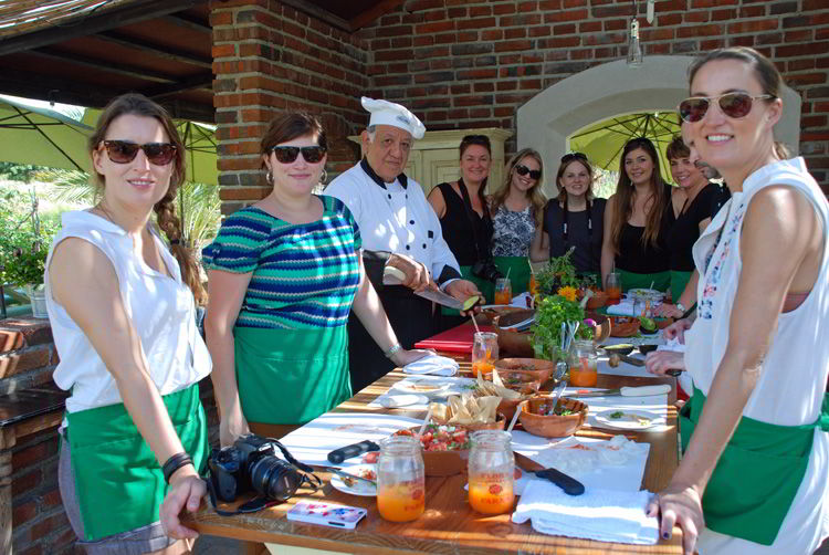 An image of a group of people in enjoying a cooking class at Flora Farms Field Kitchen in Cabo San Lucas, Mexico.