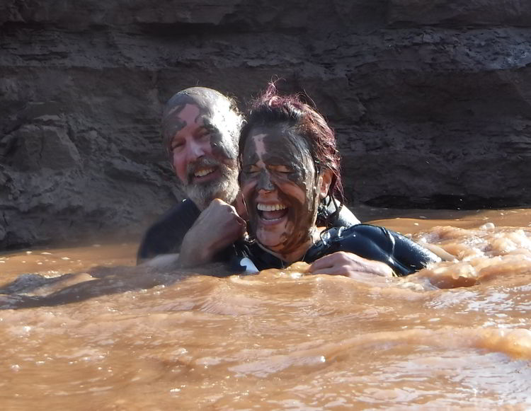 An image of two people covered in mud swimming in the Schubenacadie River in Nova Scotia.