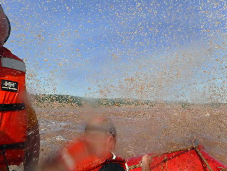 An image of water splashing into the zodiac boat while tidal bore rafting on the Schubenacadie River in Nova Scotia.
