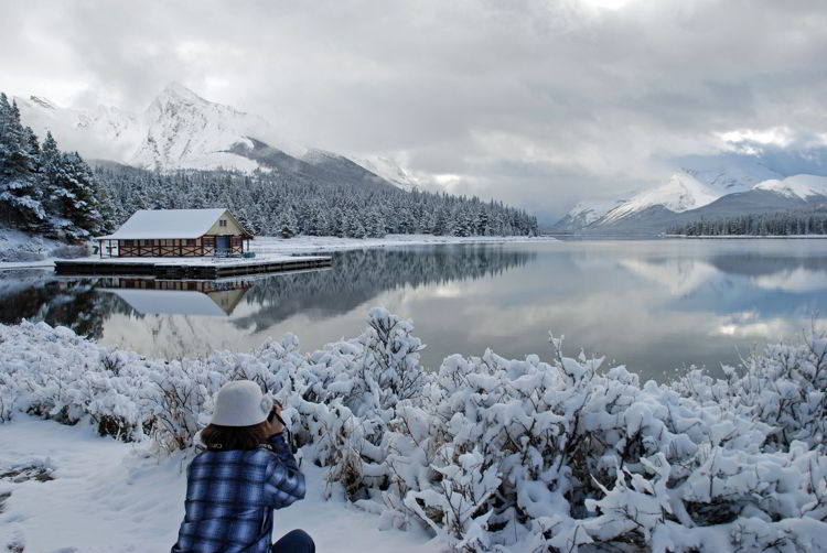 An image of a woman taking a picture of snowy Maligne Lake in Jasper in winter.