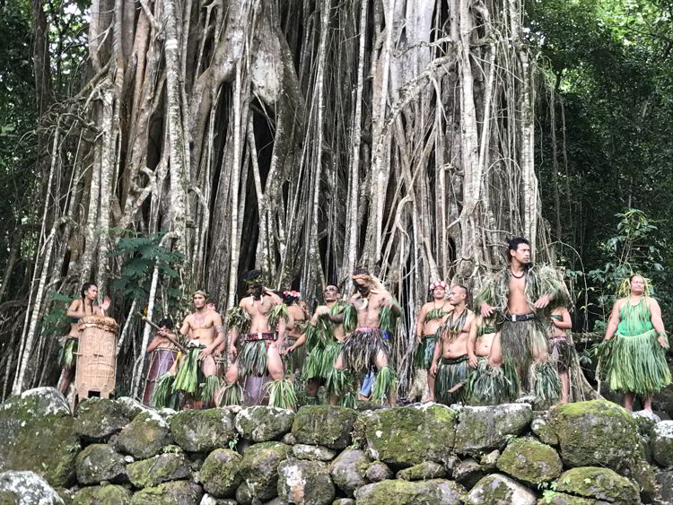An image of dancers performing in front of a banyan tree on the island of Nuka Hiva in the Marquesas Islands of French Polynesia.
