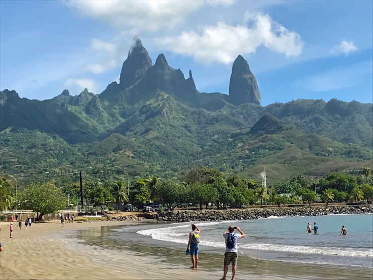 An image two people walking on a beach on Ua Pou Island, the third largest of the Marquesas Islands of French Polynesia.
