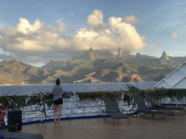 An image of a person standing on the deck of Aranui 5 looking at Ua Pou Island in the Marquesas Islands of French Polynesia.