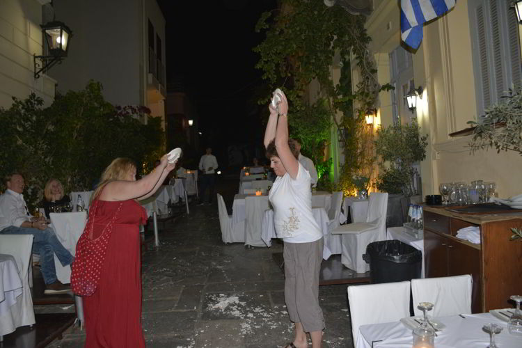 An image of two women braking plates at Adrianos restaurant in Athens, Greece.
