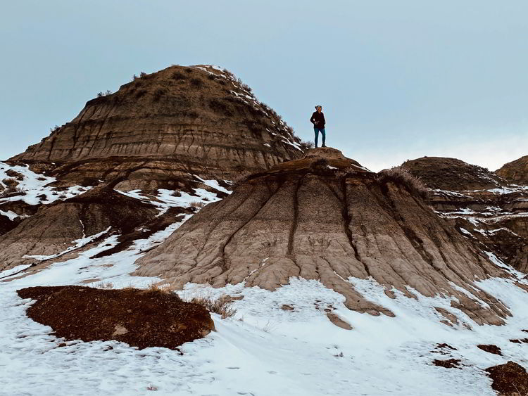 An image of a woman hiking in the badlands near Drumheller in the winter - things to do in Drumheller.