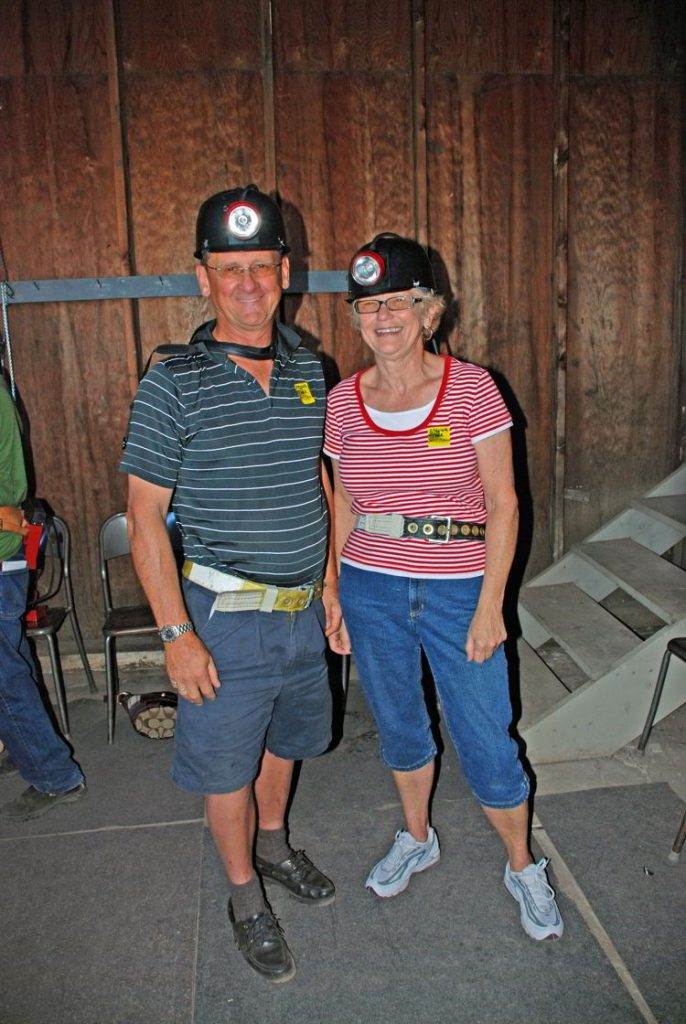 An image of a couple wearing hardhats for a tour of Atlas Coal Mine.