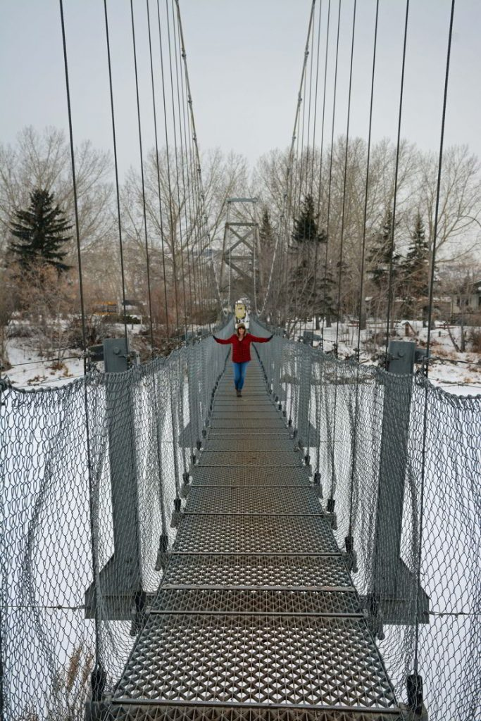An image of a woman standing on the Star Mine Suspension Bridge near Drumheller, Alberta in the winter.