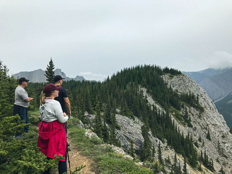 An image of three people taking in the view along the first section of the Heart Mountain Horseshoe trail near Canmore, Alberta.