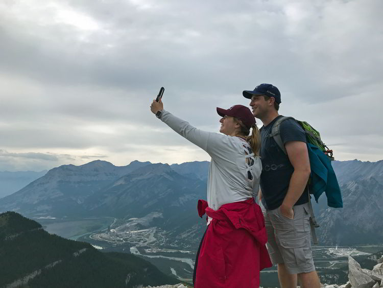 An image of a couple taking a selfie on the third summit of the Heart Mountain Horseshoe hike near Canmore, Alberta.