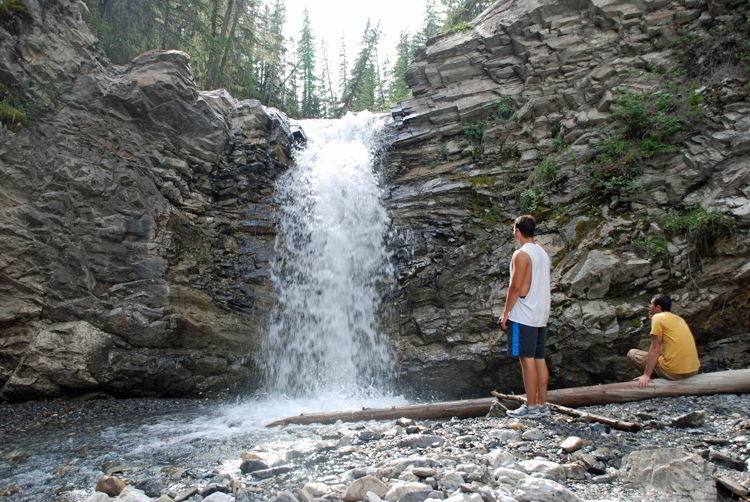 An image of two men near a waterfall on the Allstones Creek hike in Bighorn Backcountry, Alberta, Canada.