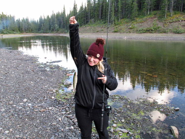 An image of a woman holding a brown trout at Allstones Lake in Alberta, Canada.