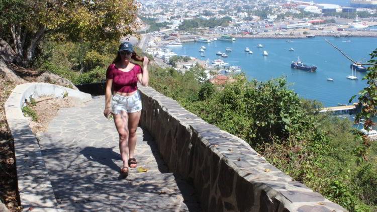 An image of a woman walking up the steps to El Faro in Mazatlan.
