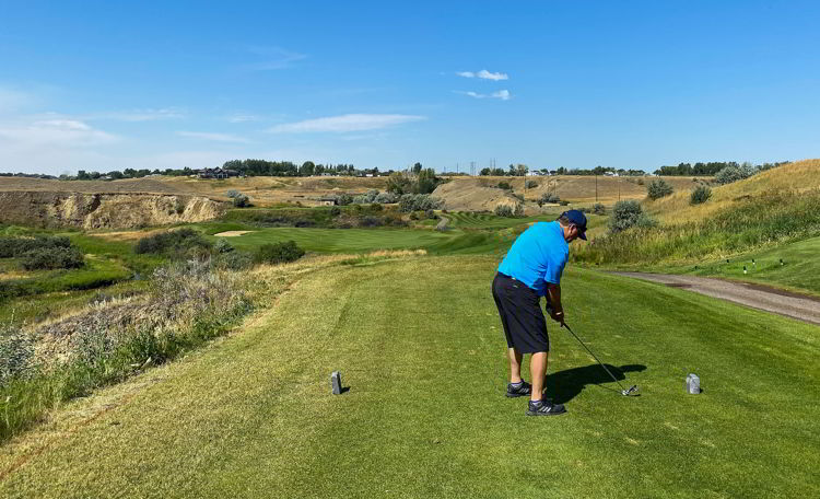 An image of a man teeing off at Desrt Blume Golf Course in Medicine Hat, Alberta, Canada - Things to do in Medicine Hat.